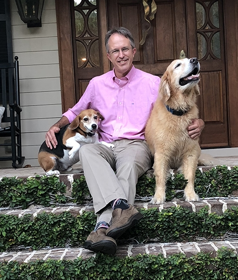 Man with 2 dogs on front porch steps